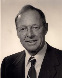 Formal portrait of middle aged man in business suit and glasses