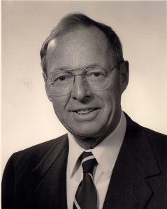 Portrait officiel d'un homme d'âge moyen portant complet et lunettes.