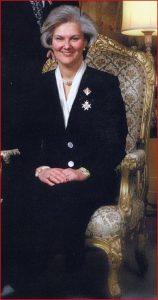Portrait officiel d'une femme aux cheveux grisonnants portant un tailleur à jupe longue et posant assise dans un fauteuil richement décoré.