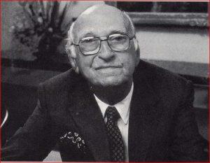 Portrait officiel d'un homme chauve portant un complet et des lunettes.