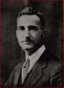 Portrait officiel d'un homme portant une moustache et un costume.