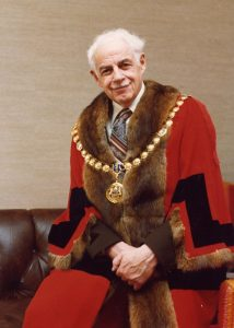 Formal portrait of grey haired man wearing mayoral robes and chain of office – the robes are red with brown fur trim around the collar, down the front and the ends of the sleeves