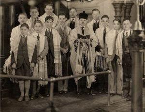 13 boys and men in suits and with prayer shawls over their shoulders with the Rabbi holding an opened prayer book