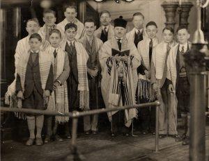Treize hommes et garçons en complet-veston portant des châles de prière alors que le rabbin tient un livre de prières ouvert.