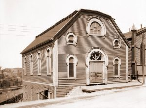 A wooden building with a central door and five windows with rounded arches over them.
