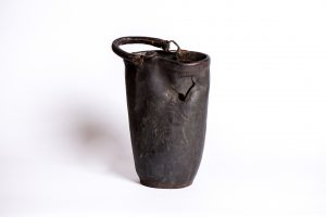 Photograph of an oval, black leather fire bucket on a white background. The bucket has a crack in it, clearly showing that it is old and worn.