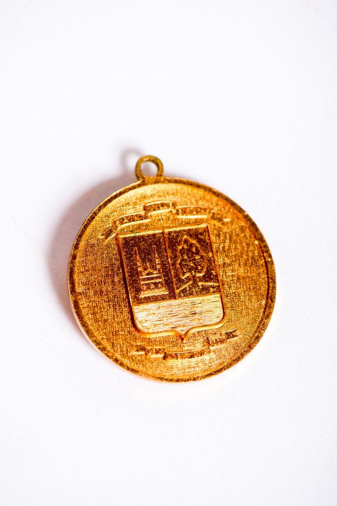 Photographie d'un médaillon honorifique de couleur dorée sur fond blanc illustrant les armoiries de la Ville de Saint-Eustache, soit une église, un chêne et une rivière.