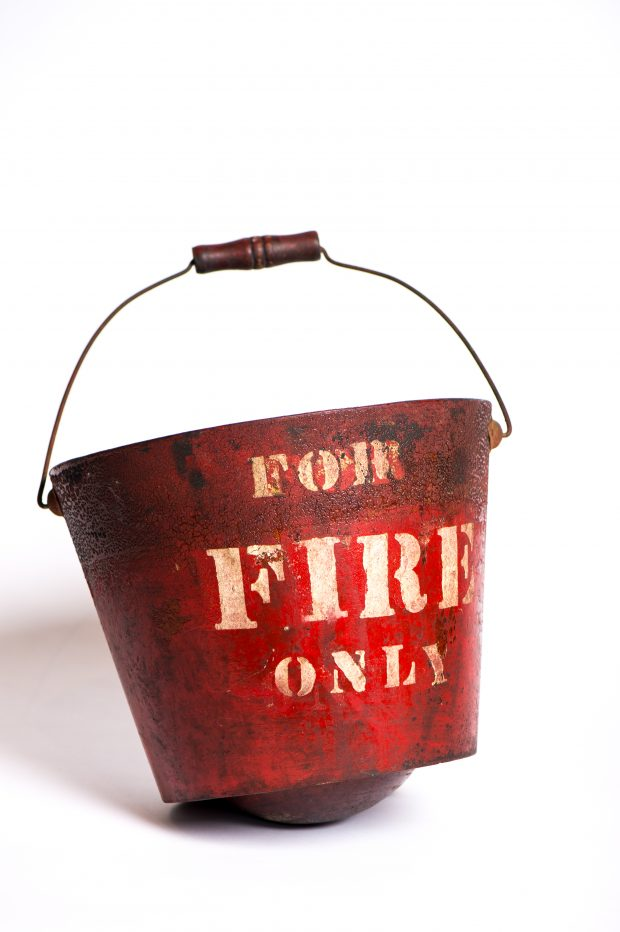 Photograph of a red round-bottomed fire bucket bearing the English words 'For fire only' in block letters.