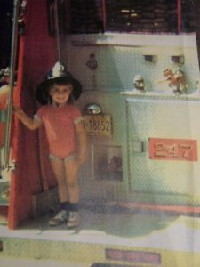 Colour photograph of a four-year-old girl standing at the back of a fire truck, smiling and wearing a firefighter's helmet.