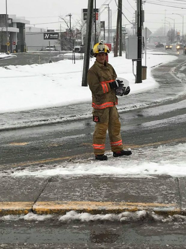 Photograph of a firefighter in his firefighting gear; he is at an intersection, holding a bucket to collect donations from motorists.