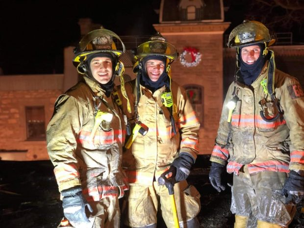 Photograph of three smiling firefighters in firefighting gear, in front of a church, at night, under the lights.
