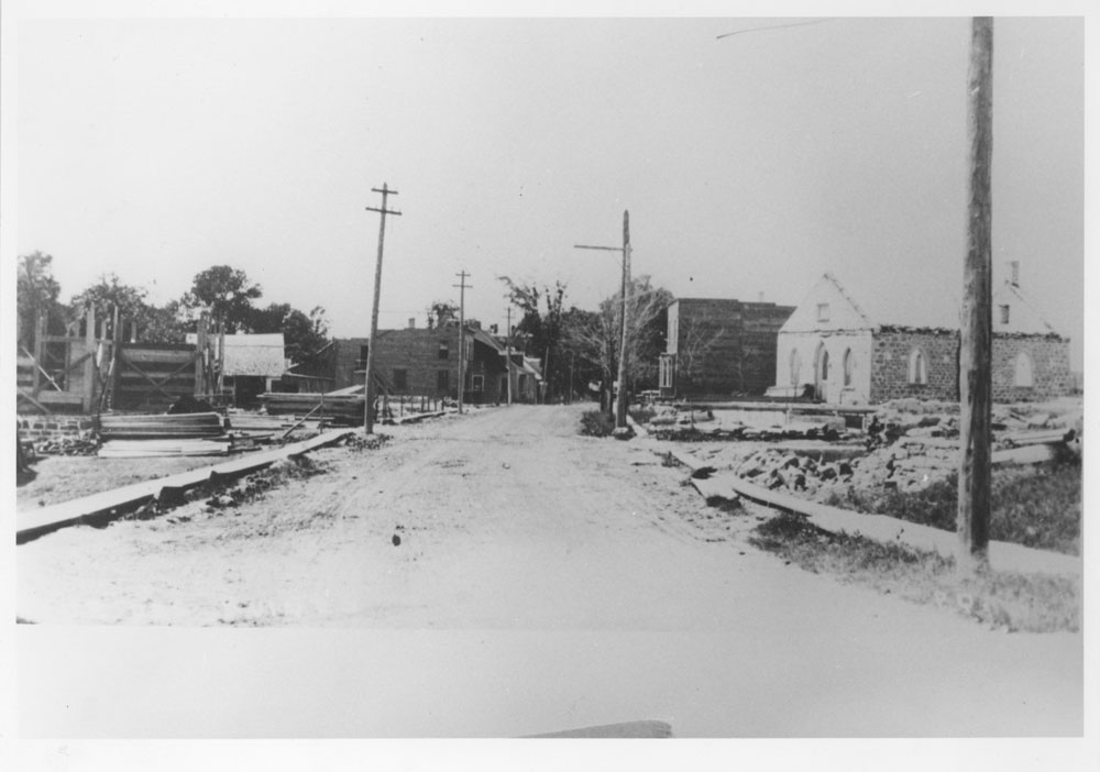 Black and white photograph of a street that has been completely devastated by fire. Houses, businesses and other buildings have been seriously damaged.