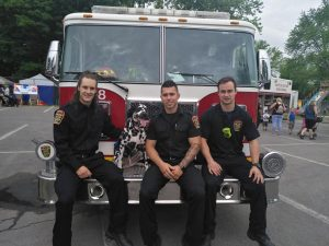 Photograph of three men in firefighters' office uniforms, sitting on the front of a fire truck with a Dalmatian.