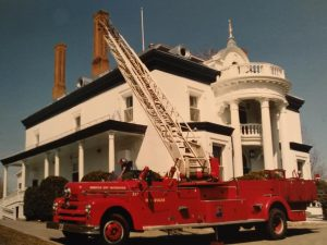 Photograph of a red convertible fire truck raising its aerial ladder in front of a white 19th-century mansion.