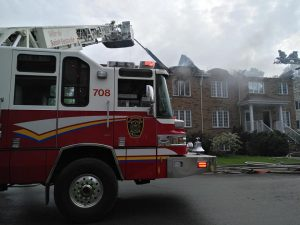 Photograph of a red and white fire truck in front of a row of townhouses on fire. The aerial ladder is pointed toward the location of the fire.