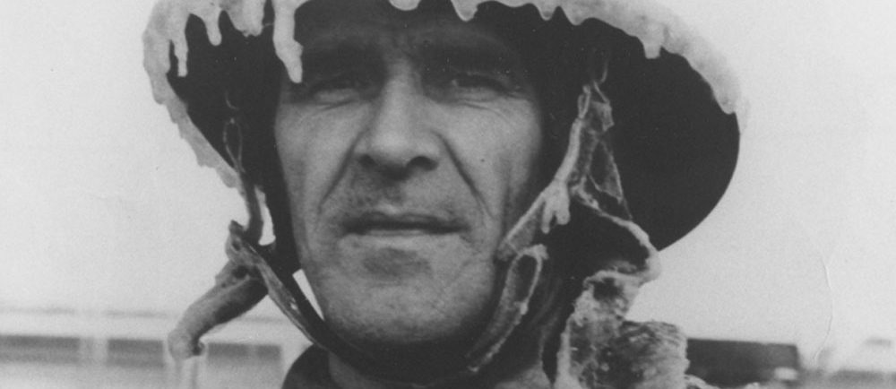 Black and white photograph of a peaceful-faced man wearing ice-covered firefighter's gear.