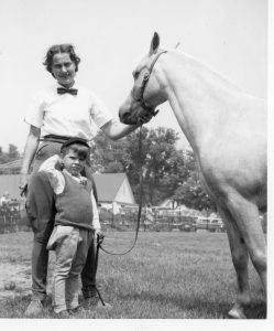 A black and white photograph of a woman, young boy and a horse standing in a park; several cars, buildings and people are in the background behind a temporary fence