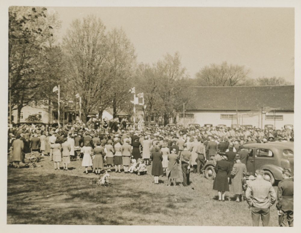 A somewhat blurry black and white photograph of a large gathering of people, most with their backs facing the camera, in a park surrounding a raised platform at the left side with four posts bearing Union Jack flags, upon which are seated about a dozen people; large white clad building and several trees and houses in the background