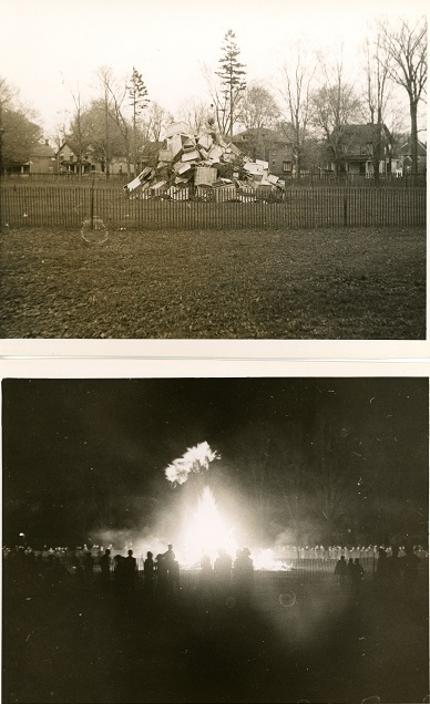 Two black and white photographs of a bonfire in a park setting; top image taken during the day depicts a large pile of wooden items surrounded by a temporary snow fence; bottom photo take at night depicts a lit bonfire with numerous people gathered around