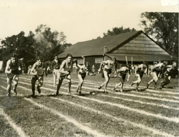 A black and white photograph of group of nine boys wearing shorts and tank tops running in lanes painted on grass in a park setting; large rectangular wooden building with a few spectators and cars in the background