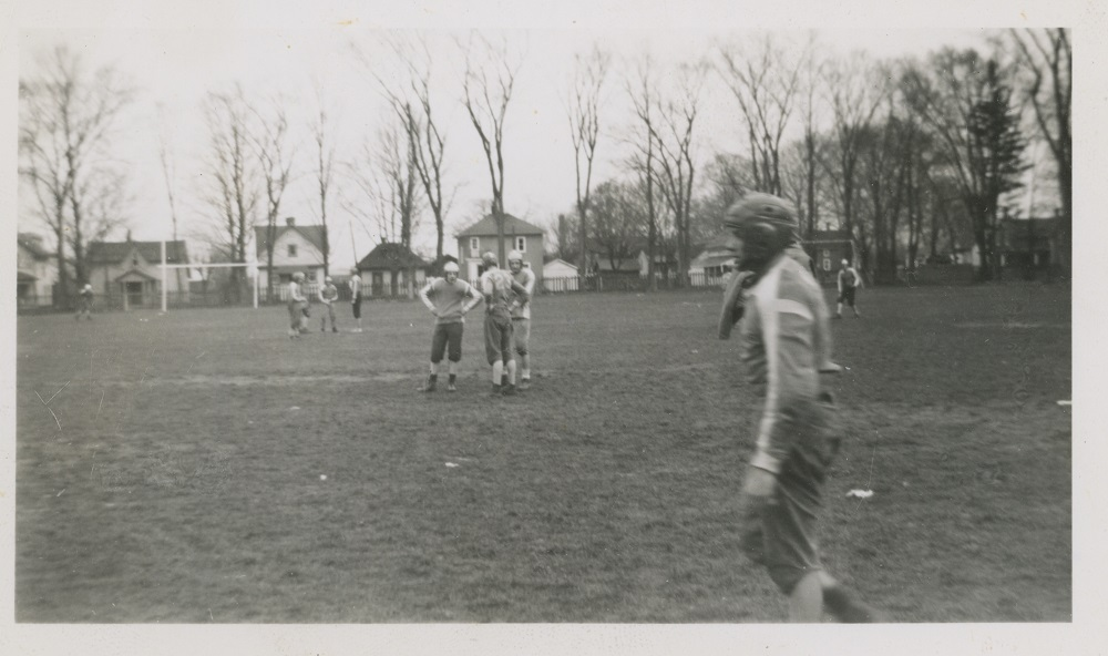 A black and white photograph of a group of boys in football uniforms spread out across a grass field; houses are visible in the background behind a picket fence and a row of trees