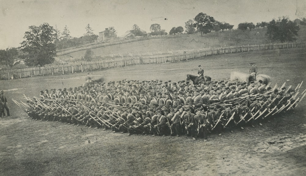 A black and white photograph of soldiers in a field with rifles drawn in a tight, square formation, with three horses, two are partially blurred, at the back; two men look on from the left; a farm and wooden fencing is visible in the background