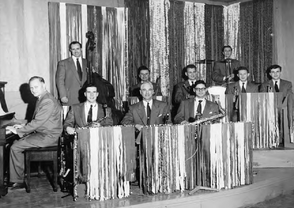 A somewhat blurry black and white photograph of a ten piece male band wearing dress suits and ties, sitting behind covered music stands, on two levels on a raised double platform; the music stands and background covered by panels of paper or fabric vertical strips giving a shimmering effect; piano and player at bottom left