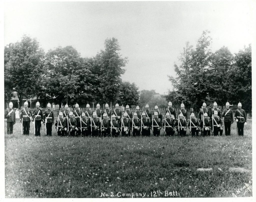 A black and white photograph of male soldiers posing in a park setting, in two rows, front row on right knee; all holding a rifle or sword and wear uniforms with helmet containing a spike on top; wooden picket fence, trees and obscured houses in background