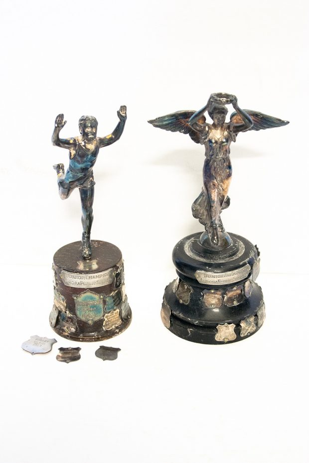 Two small silver trophies on wooden bases covered with engraved silver shields; the one at left depicts a male figure running with both arms raised; the one at right features a winged female figure in flowing dress with raised arms holding a wreath with both hands; three loose silver engraved shields sit in front of the trophy at left