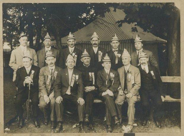 A black and white photograph of a group of 13 men in suits wearing the same triangular shaped hats and matching pins and ribbons pose in two rows, front row seated on bench, in front of a striped marquee in a treed setting