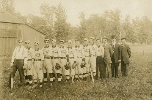 A black and white photograph of fourteen men, some wearing baseball gloves and others holding bats, posing in a straight line on a grass field with trees and a wooden building in the background; ten men are wearing baseball uniforms inscribed with
