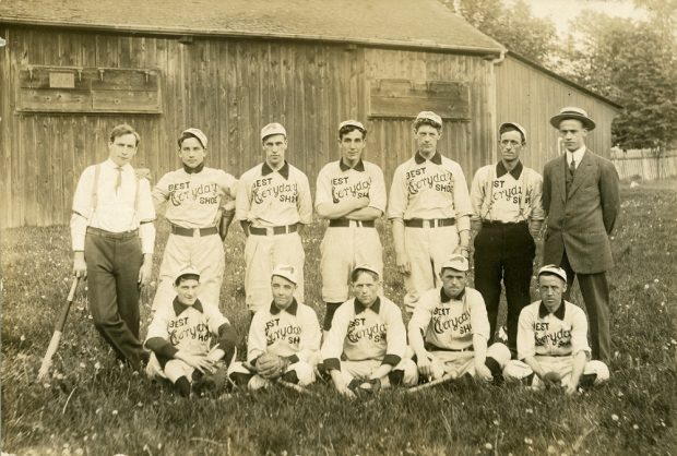A black and white photo of a male baseball team posing in two rows, with the front row seated on the grass, in front of a wooden building; 10 men wear uniforms with the BEST Everyday SHOE written on front, two men stand at either end of back row in dress clothing