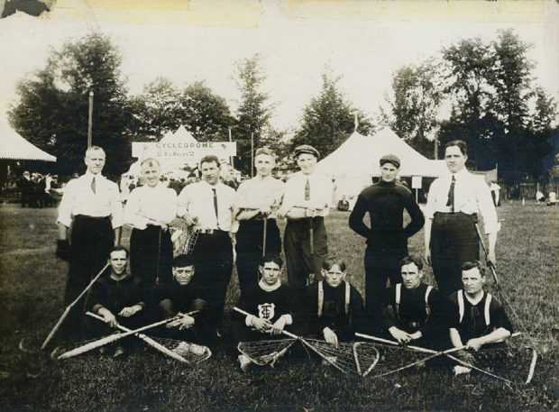 A black and white photograph of a lacrosse team posing in two rows in Town Park; front row 6 men seated on grass with lacrosse sticks crossed over legs, 7 men standing in a row behind; background park setting with three large white tents and people milling around