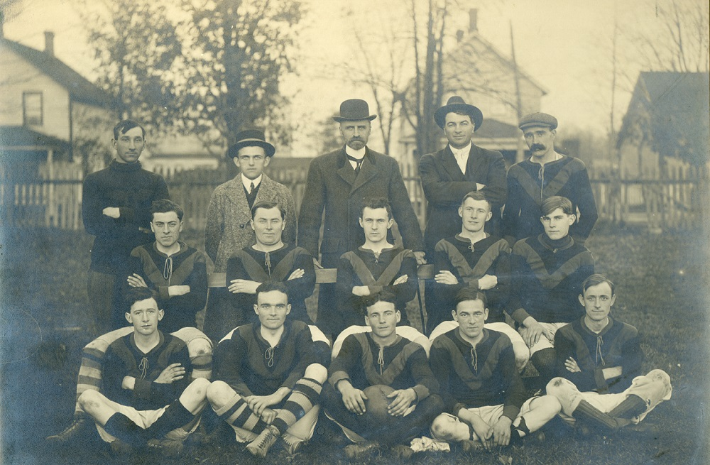 A black and white photograph of a football (soccer) team posing in three rows, five in uniform sit on grass with middle boy holding a ball, second row of 5 in uniform seated on a bench, last row of 5 standing behind; four houses and a picket fence visible in background