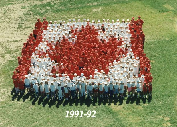 A colour photograph taken from above of a group of students dressed in red or white standing on grass in the formation of the Canadian flag
