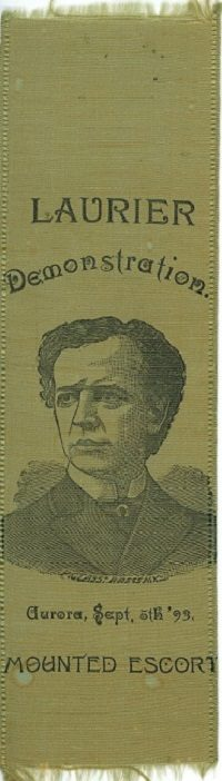 A green satin ribbon with frayed top and bottom edges, printed with a black ink portrait of the head and shoulders of a man glancing to his right and wearing a double breasted suit jacket and white shirt with high collar; black ink text above portrait reads: LAURIER Demonstration, and below Aurora, Sept. 5th '93 MOUNTED ESCORT