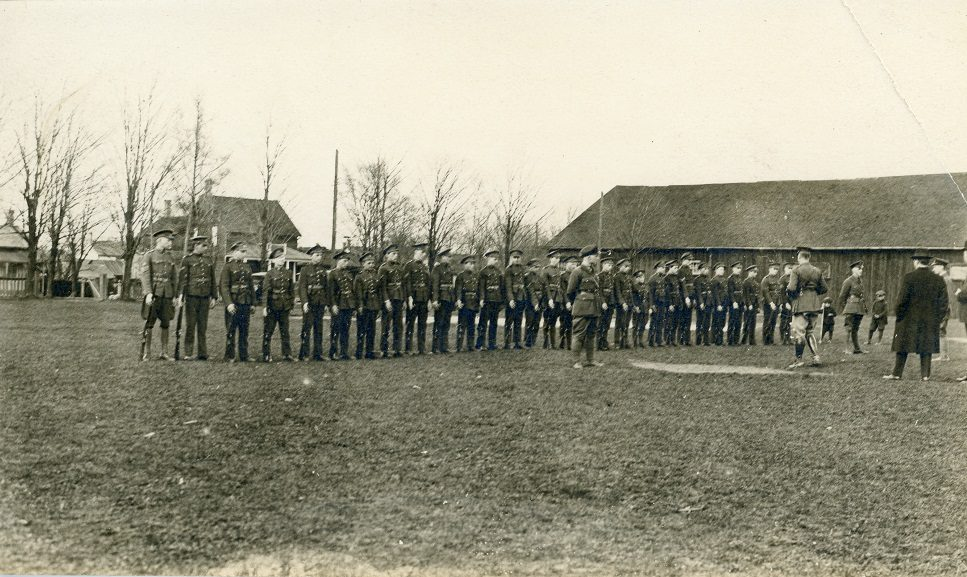 A black and white photograph of a group of young boys in uniforms with rifles, lined up in a single row; two small boys and several men, some in uniform, observe from the right side; a large rectangular wooden building and several houses visible in the background