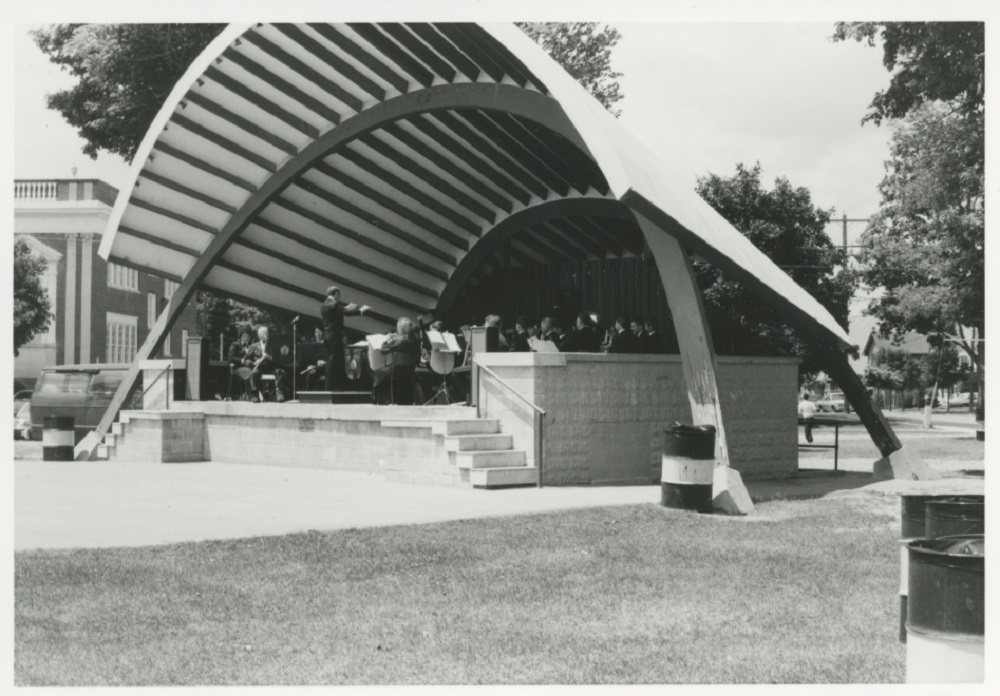 A black and white photograph of a bandshell consisting of a raised concrete platform reached via two sets of five stairs on either end at the front, the whole covered by a parabolic shaped roof supported by two curved arches; a band performs on the platform