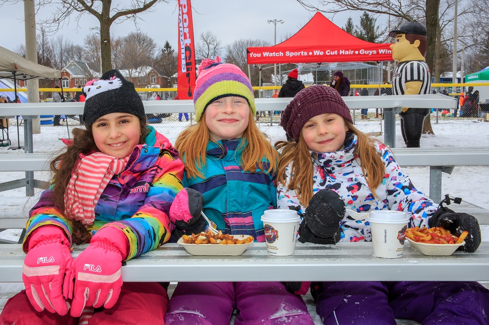 A colour photograph of three girls in brightly coloured snowsuits sitting on bleachers in a park; two girls have a container of french fries and a covered paper beverage container in front of them; an inflatable figure of a referee, several people and tents in the background