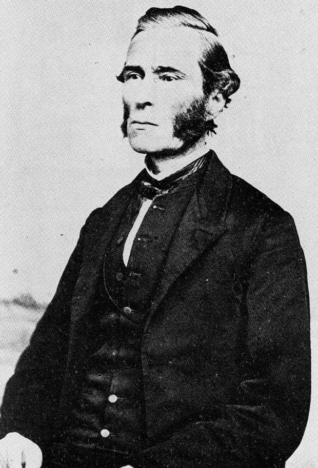 A black and white photograph of a man pictured from the waist up, wearing a dark coloured jacket, waistcoat and pants with white shirt and dark tie; man is posed slightly off centre facing to his right and sports a sidebeard