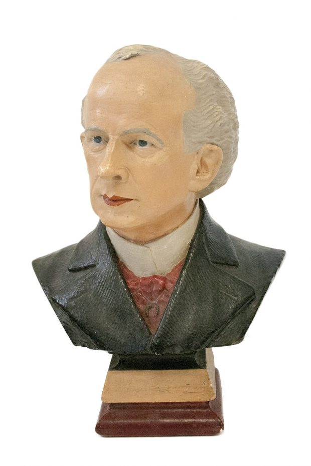 A coloured plaster bust of a man with receding grey hair wearing a white shirt, red cravat and black jacket