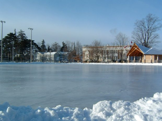 A colour photograph of a large outdoor ice rink in a park surrounded by small banks of snow; a bandstand, school building, houses and baseball diamond visible in the background