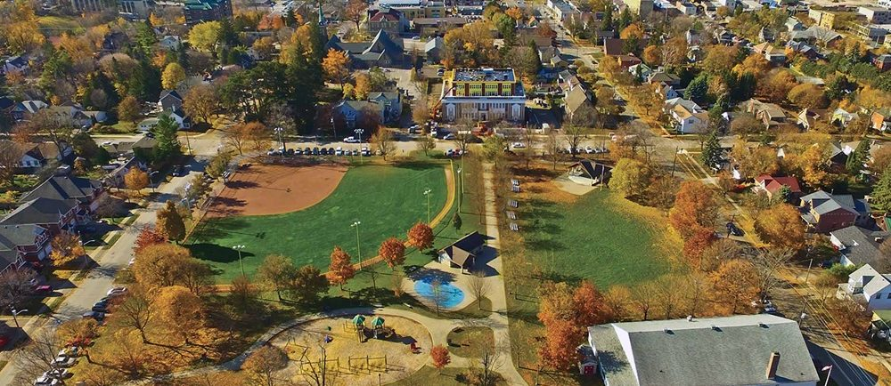 A colour image of a birds eye view of a park taken in the fall showing trees a playground and splash pad in the lower left, large rectangular white clad building with grey roof lower right, covered bandstand upper right and baseball diamond with lighting upper left; houses and buildings are visible in the background