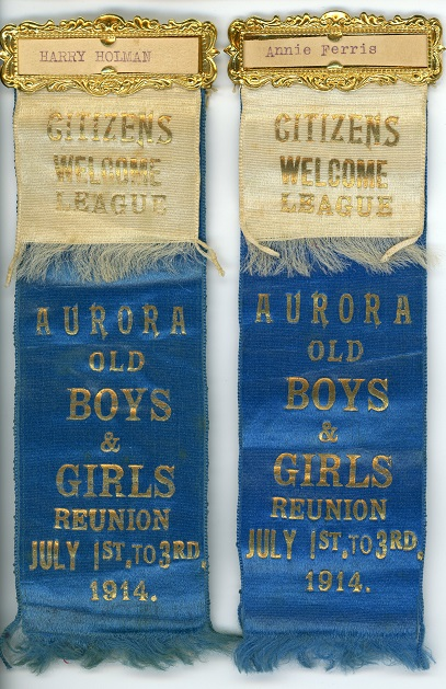 A pair of blue silk ribbons with gold lettering each bearing a secondary overlay of cream silk ribbon with gold lettering both ribbons bound together at the top with a gold rectangular frame enclosing a piece of paper with a typed name