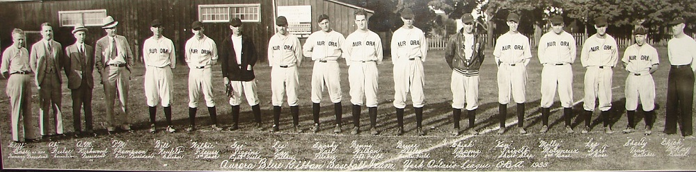 A black and white panoramic photograph of a group of 17 men standing in a straight line in a grass field, all put four men at left are wearing baseball uniforms; name of each man written in white ink appears directly beneath; trees and wooden building appear in background