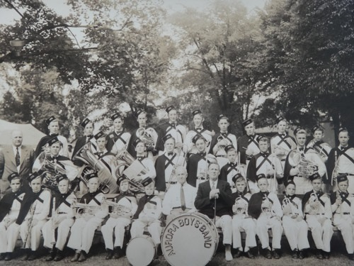 A black and white photograph of a boys band dressed in uniforms and most holding instruments arranged in three rows, front row sitting; taken in a park setting