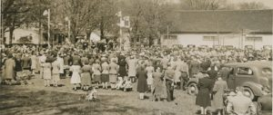 A somewhat blurry black and white photograph of a large gathering of people, most with their backs facing the camera, in a park surrounding a raised platform at the left side with four posts bearing Union Jack flags, upon which are seated about a dozen people; large white clad building and several trees and houses in the background. In the foreground there are two boys on the grass dressed in military style uniform.