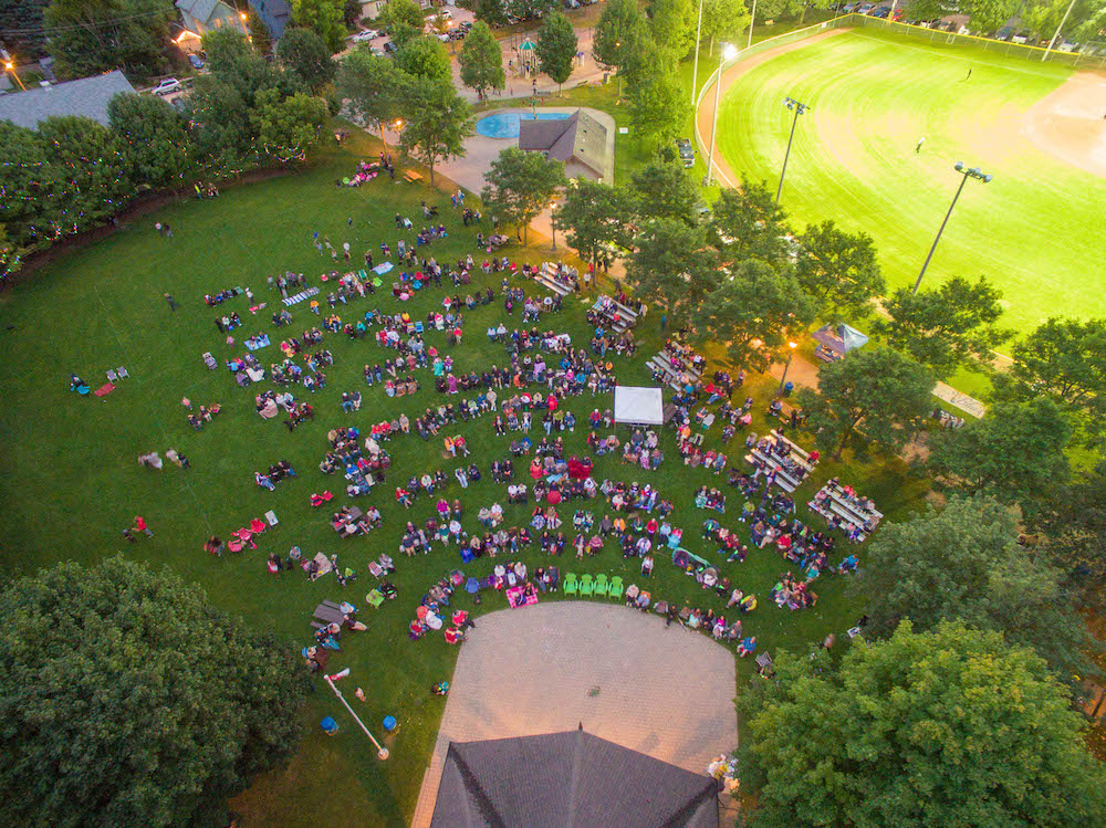 A colour image taken from a drone that gives a bird's eye view of a large park that has a covered performance stage, splash pad and baseball diamond visible. The lawn in front of the performance stage is filled with people who are watching the stage and sitting on chairs or bleachers.