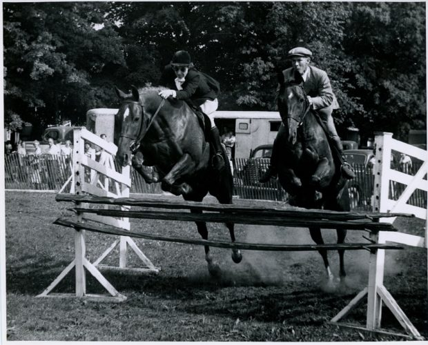 A black and white photograph of two horses and riders in a park that are simultaneously jumping over a piece of wood that is raised approximately 1 metre off the ground and is being held by two white wooden stands that are parallel to one another. The rider on the right is a man and the rider on the left is a woman. In the background people are looking on from the other side of a chest height wooden fence.