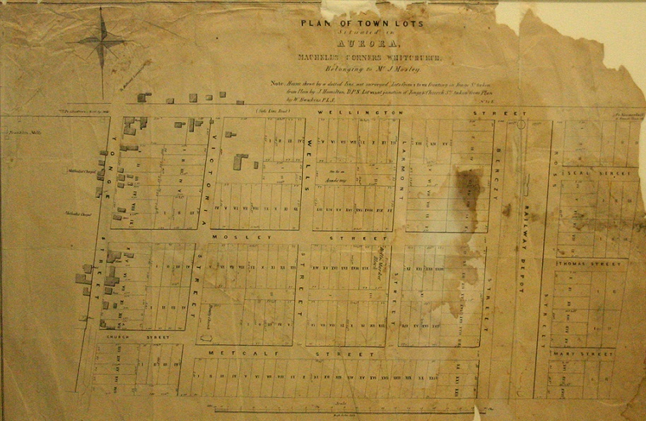 An old creased, stained and torn map of building lots in Aurora laid out on a grid depicting lot numbers and street names